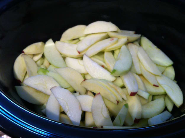 Lay the sliced apples in the slow cooker.