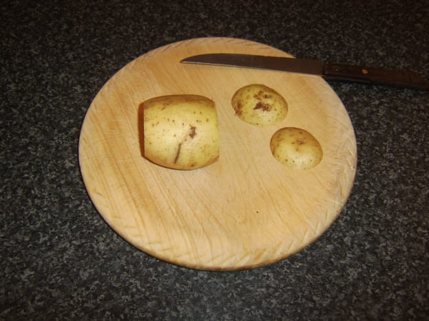 Two end slices are cut from baking potato