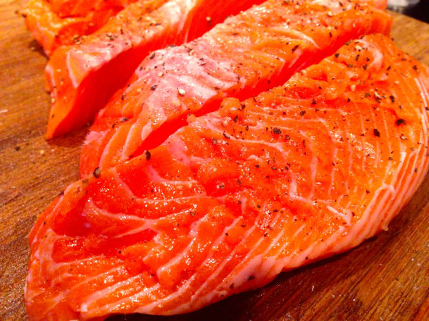 Season the cut salmon fillet with salt and pepper.