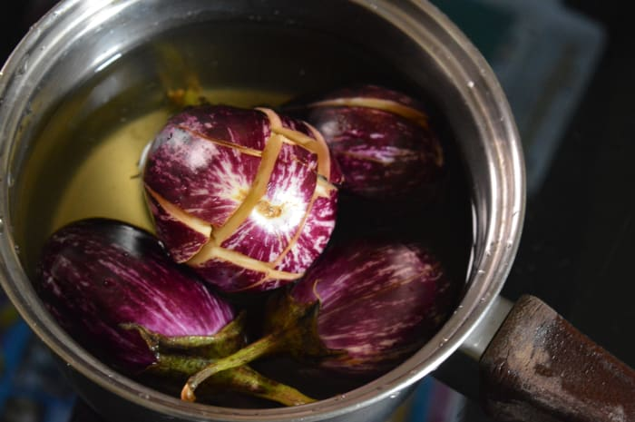 Step one: Slit the eggplants vertically and immerse in water.