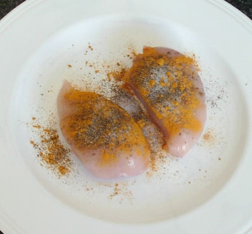 Turmeric and black pepper are scattered over chicken breasts