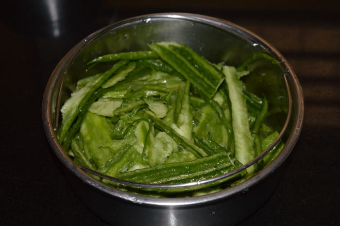 Collect the ridge gourd peels in a container.