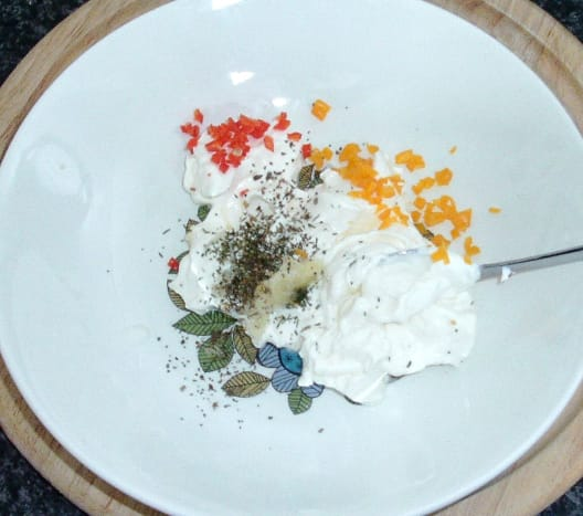 Herbs and spices are added to cream cheese