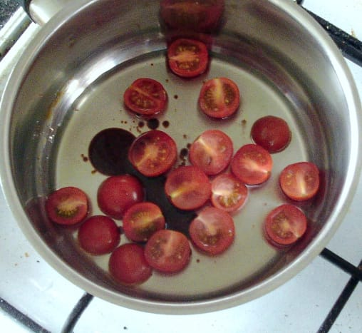 Tomato sauce ingredients are added to a small saucepan