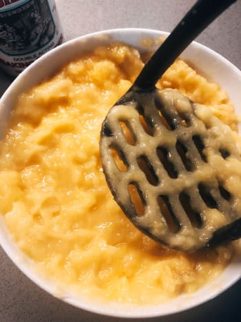 In a bowl, mash the bananas using a waffle head masher.