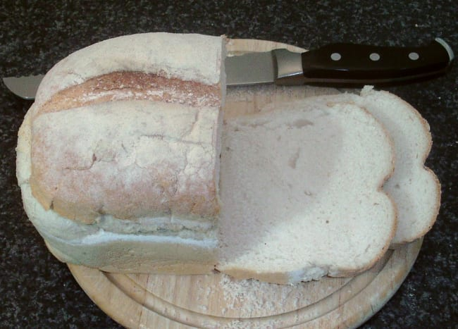 Slices are cut from a farmhouse loaf