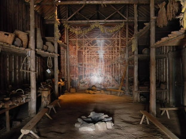 Inside a 15th century Iroquois Longhouse in Ontario, Canada. Notice the wooden benches used.