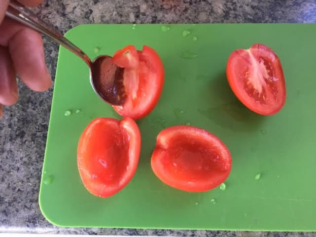 Using a spoon to de-seed the plum tomatoes