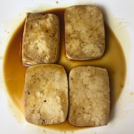 Lay the tofu slices out flat either on a plate or in a bag, then add the shoyu sauce. Let them marinate while you prepare the remaining ingredients, and flip the tofu pieces after about 12 minutes. You can also marinate them overnight.