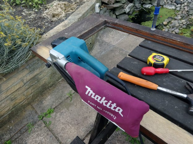Using a belt sander to take the surface back to the bare wood.