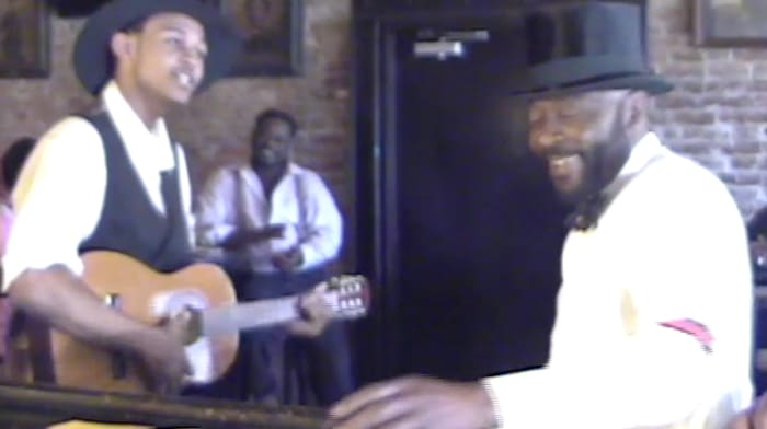 """This photo is a reenactment of a young W.C. Handy (guitar in hand) demonstrating his new blues song entitled """"Mr. Crump Blues"""" to a receptive audience.  (Reenactment)"""