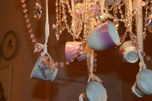 Hanging small teacups from a chandelier is such a lovely idea!