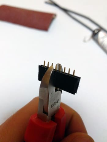 Using the cutting pliers, cut at the middle of the 5th pin if you're building a 4-pin connector. General rule: cut at the n + 1/2 pin for a connector with n pins.