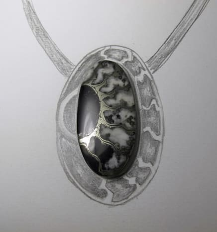 Lisa Barth sketches a rough setting and backplate design around the ammonite fossil to echo and extend its pattern onto the silver with syringe clay.