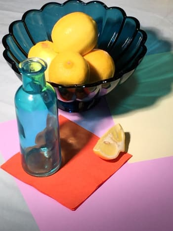"A still life set up with turquoise blue glass and lemons, for the painting ""Lemons and Teal""."