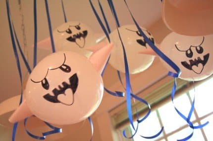 A gaggle of Boo balloons with paper cone arms.