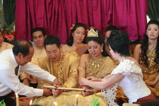 The couple kneels while holding a sheathed sword as their guests bestow blessings by tying a red string around each of their wrists.