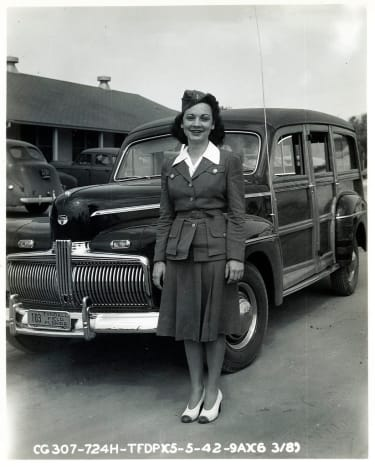 Woman standing in front of 1942 Ford Woodie during World War II.