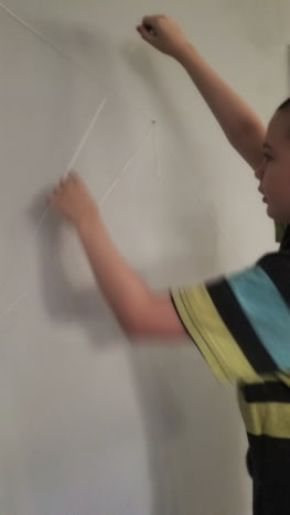 My son creating his dental floss and thread spider web.