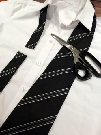 Cut the tie to fit the Clark Kent costume.