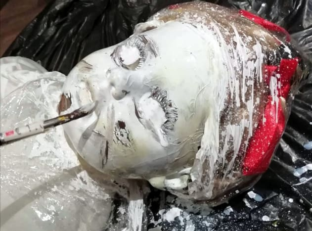 Here I paint the doll's head white after covering its eyes with tape.