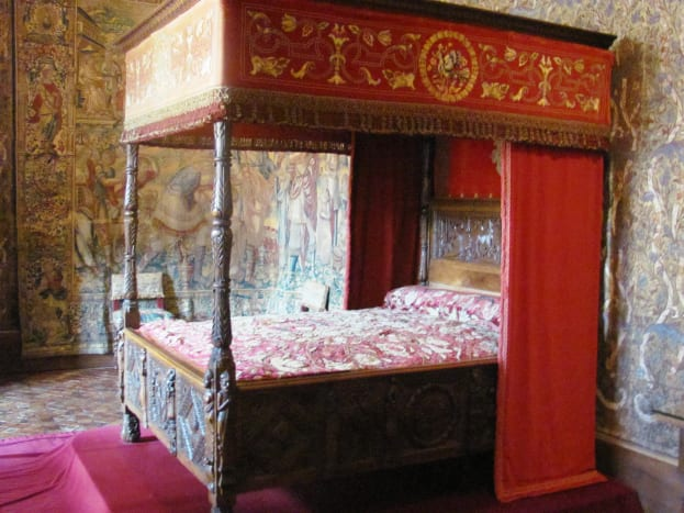 Catherine de' Medici's bedroom features rare Flanders tapestries, an exquisite wooden ceiling, and this four-poster Renaissance bed.