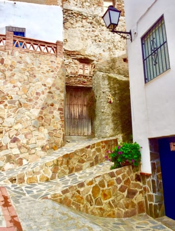 Street view from the upper part of the village, with steps and contrasting walls of rough stone against whitewashed walls.