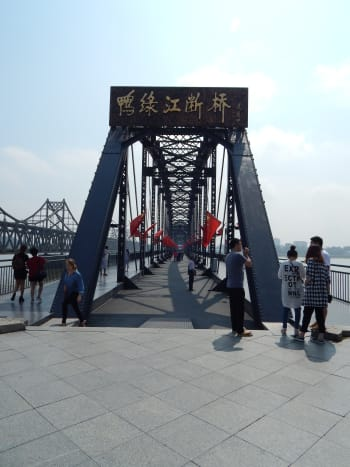 The bridge entrance looks grand, lined each side by patriotic Chinese flags. To the left, you can see the Sino-Korean friendship bridge, which still connects China and North Korea.