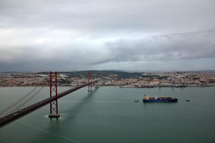 Lisbon and the 25 de Abril Bridge whose reddish tint remind me of the Golden Gate