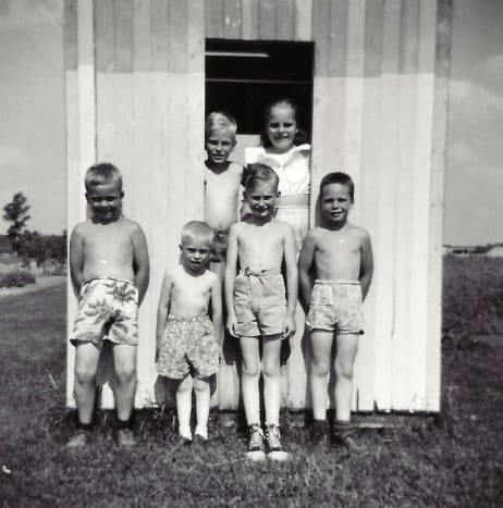 My cousins, brothers and me in the playhouse my dad built for us.  This was prior to it being finished with actual windows and a door.