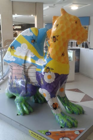 Buzz, depicting bee hives, bees in the sky with clouds and sunbeams, honeycomb, lavender & daisies.  Designed to reflect the beauty of the Norfolk countryside, she stands in the shopping mall.