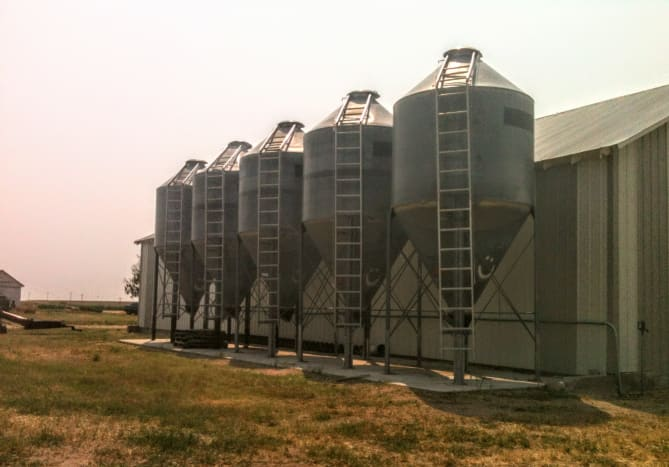 This row of 5 small vintage bins may not be especially attractive, but they function well. Several spokes and cross-bracing help stabilize the structure, which has a shorter tank and longer hopper than some.