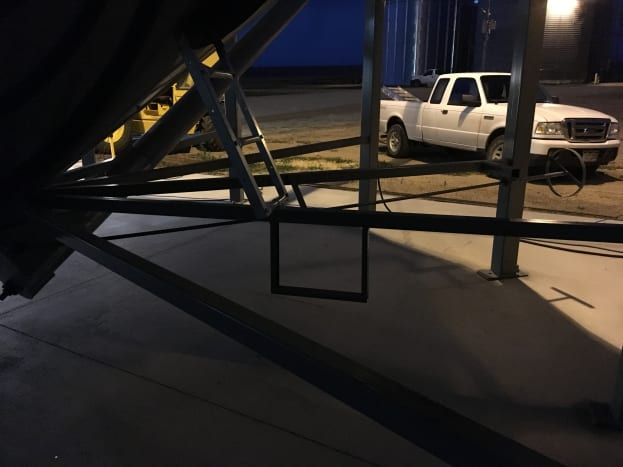 A step and short ladder are provided to access a manhole used for servicing the hopper when it is empty.