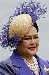 Queen SiriKit (Queen of Thailand) wearing a multi-strand pearl necklace with a white hat and purple plumes and a purple suit