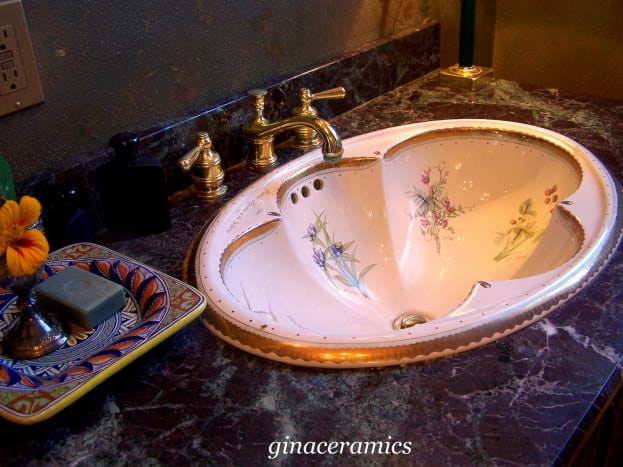 pink bathroom sink with exquisite floral design and gold accents