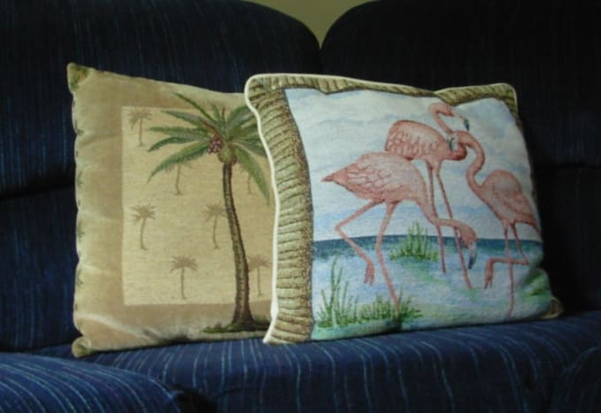 A throw pillow depicts flamingos.