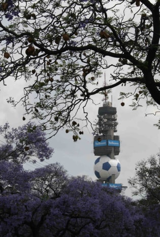 "Pretoria is a ""proud host City"" of the 2010 Fifa World Cup - symbolised by this soccer ball on the Telkom tower, rising above the jacaranda blossoms"