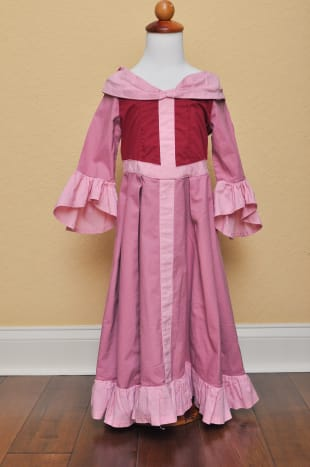 Front view. The contrast pink stripes were doubled strips of fabric sewn right on to the front of the dress. Whether you use a v-front pattern or one with a rounded waistline, you can place the strips at an angle to create the look of a v-shaped wais