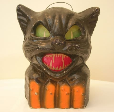 Amazingly spooky black cat with evil green eyes and vicious red teeth.