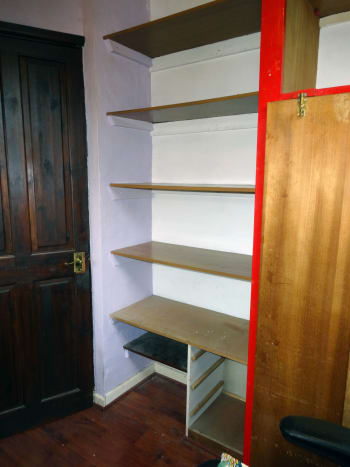 The old veneered chipboard shelving emptied, ready for dismantling and replacing