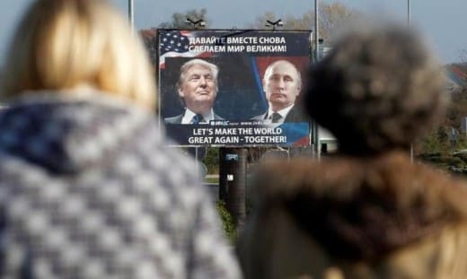 """A billboard showing a pictures of then-president elect Donald Trump and Russian President Vladimir Putin is seen through pedestrians in Danilovgrad, Montenegro, November 16, 2016."""