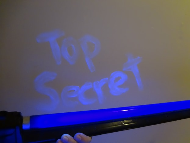 The message written in petroleum jelly glows under a blacklight.