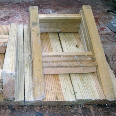 Underside view.  Boxed frame from decking offcuts with sloping sides, and decking on top.