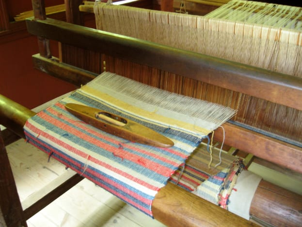 This loom with the spindle on top shows the work that goes into making patterned fabric.
