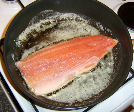 Trout fillet is laid in hot pan skin side down