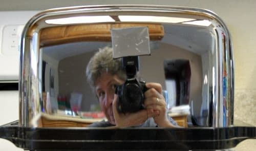 Practically any shiny object can provide a reflective surface for a self portrait. Kitchens are often full of possibilities. I looked out from behind the camera so I'd get more than just the camera in this shot.