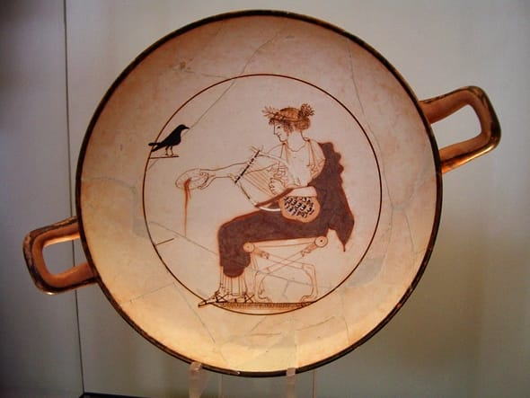 Apollo Cup, 480-470 BCE. White-ground pottery. The god has his turtleshell lyre and is pouring an offering to himself. A raven or crow -- both associated with him because of their intelligence -- looks on.