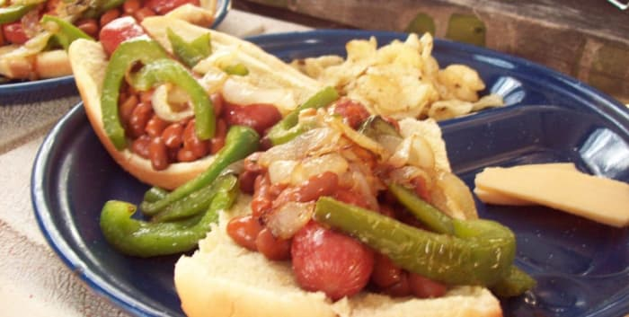 Chili hot dogs with peppers, onions and smoked Gouda cheese on the side.