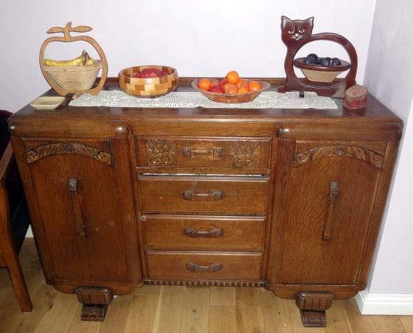 A family of wooden fruit bowls on the sideboard packed with fruit and nuts