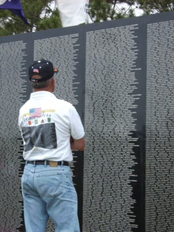My husband at the wall viewing the names of his friends